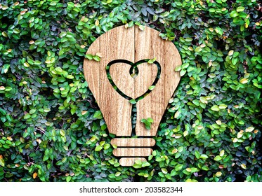 Light Bulb wood icon and heart shape inside on green leaf wall,Eco concept