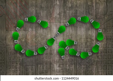 Light bulbs with green grass in form of arrow infinity recycling symbol, on dark wooden wall background, concept of ECO green energy and circular economy.