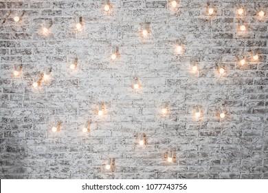 Light bulbs on white brick background. Vintage edison light bulbs garland in loft interior. Rustic Texture. Retro Whitewashed Old Brick Wall Surface. Design interior element