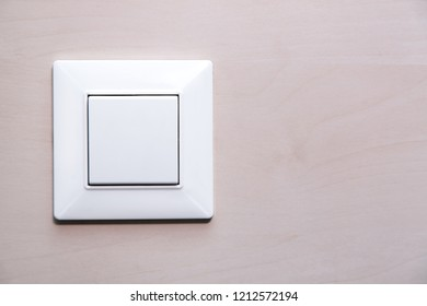 a light button switch on the wooden wall, a plastic mechanical switch close up.