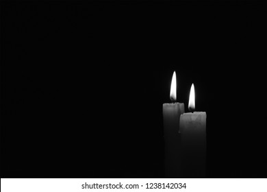 Light candle burning brightly in the black background. Candle flame. There's room for your text. Black and white photo. The concept of mourning, grief or sorrow.