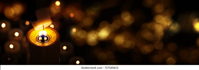 Light candle with golden bokeh