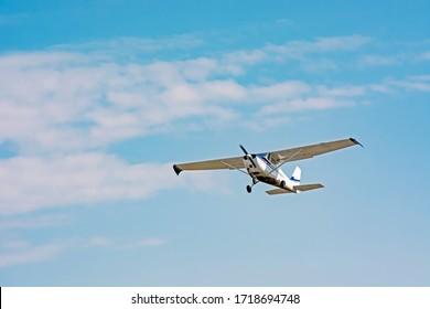 light cessna plane flies in the sky