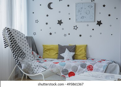 Light child bedroom with window, single bed and stars on the wall