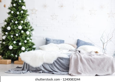 Light Christmas interior room decorated with Christmas tree, gift boxes, white walls and white coverlet. Christmas interiors with bed, fir-tree, pillows.