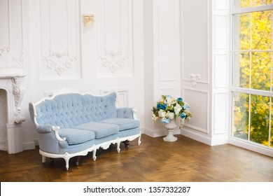 light classic royal interior with blue soft sofa with fabric upholstery. Elegant royal luxury interior with white walls and blue sofa