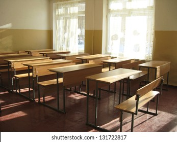 Light classroom with a lot of desks. School is waiting. Holidays started. The place where pupils receive knowledge