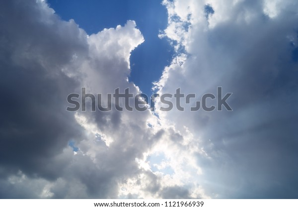 Light in the clouds, sunlight on the background of clouds.  Divine light from the sky cleaves the rays of a dark cloud.
