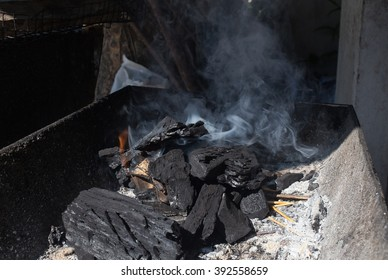 To light coals in a barbecue grill with a lot of smoke - selected focus, narrow depth of field