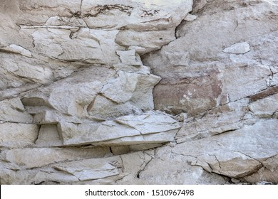 Light coarse natural rock stone background. Mining cliff rough front surface. Big limestone stack backdrop. Heavy grunge damage granite block texture. Crack antique medieval marble facade  for design