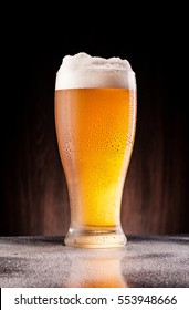 light cold beer in frosty glass over dark wooden background