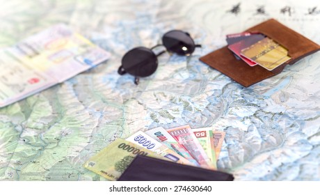 Light color composition on travel topic.  Unfolded detailed topographic map exotic Asian cash notes credit cards sunglasses passport entry stamps many