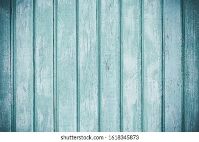 Light colored timber fence with peeling paint. Shabby decrepit wooden boards. Wood lamellas. Blue rough painted planks surface. Abstract wallpaper. Vintage background. Texture element.