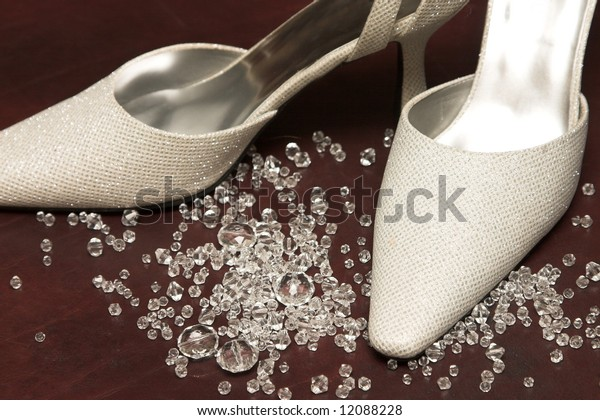 Light Colored wedding shoes amongst glass stones