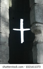 Light coming through cross shaped arrow slit in York city walls