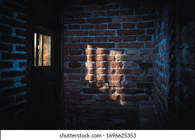 Light coming through a window on the brick wall in prison. Hight contrast dark shot