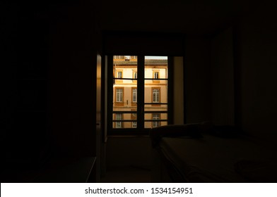 The light coming from a window, with a facade enlightened by the sunlight, in the middle of a dark room ; bright window in a dark room, with clair obscur effect, in Toulouse, France
