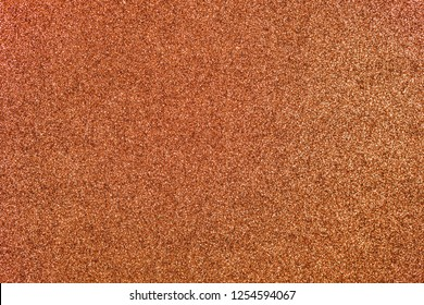 Light copper colored sand paper textured background with sparkles and glitters