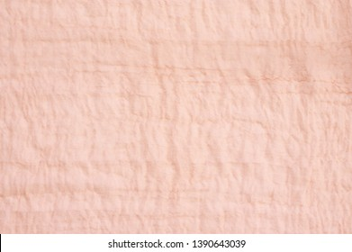 Light coral colored crash voile fabric as background.