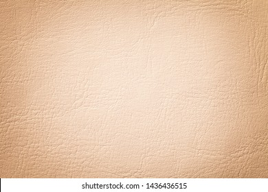 Light coral leather texture background, closeup. Beige cracked backdrop from wrinkle skin, structure of textile with vignette.