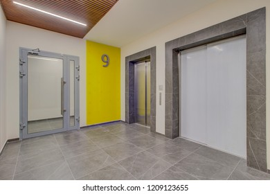 Light corridor and modern two elevator with a closed doors. There is illuminated wall.