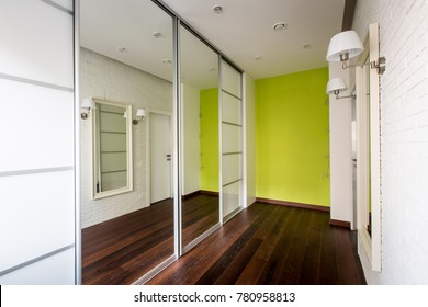 A light corridor in which there is a wardrobe with large mirrors