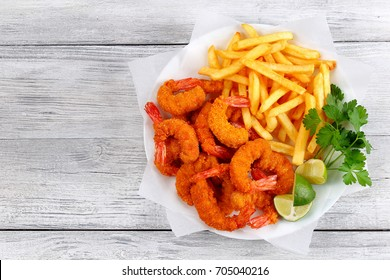 light and crispy crunchy parmesan bread crumbs coating Fried Shrimps with lime wedges, french fries and parsley on white plate on wooden table, view from above