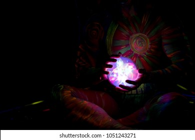 Light crystal ball is glowing up in hands of blacklight color man.