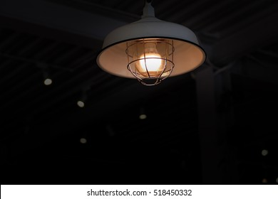 Light in the dark room. Classic lamp in the dark room. Lantern in vintage style in the dark room.