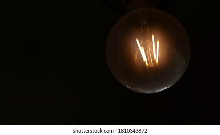 Light in darkness or old incandescent lamp with warm white for business idea and vision solution or vintage led light bulb and concept of new ideas and night decor on black background with copy space