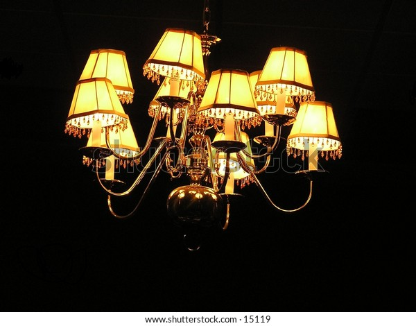 A Light In the Darkness. This Chandelier is in a  small room of a  church. and Is Accented by the total darkness around it.