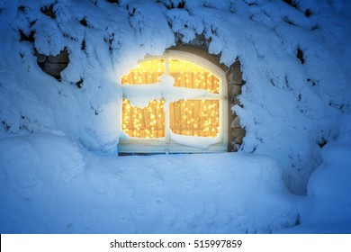 Light decoration in the window in a cold, snowy winter night. The  house walls are covered with snow. Christmas or winter background