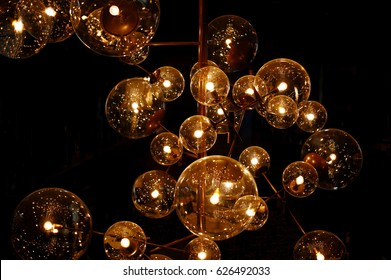 Light, design and interior. Vintage metallic lanterns. Group of lamps with interesting shape of tungsten filament. Modern lighting of cafe and restaurant. Isolated on black