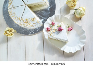 light diet layered biscuit with curd cream and cherry. cake covered with curd cream and garnished with dried roses on the white wooden background