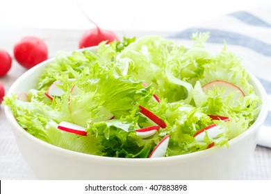 light diet salad with fresh lettuce and radish in a white bowl on wooden background