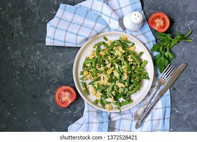 Light dinner or lunch, fried green asparagus beans with scramble egg on a white clay plate. Georgian cuisine