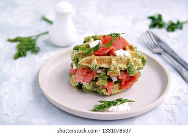 Light dinner, lunch or lunch, savory spinach snack waffles with salted salmon and cream cheese on a ceramic plate.