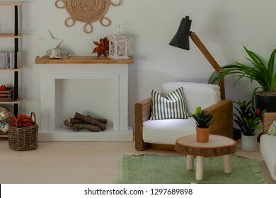 Light dollhouse room with wooden furniture and white fireplace with firewood, A cozy armchair with striped soft pillow and lit standard lamp – a comfortable place for rest or reading, Home comfort