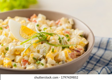 A light egg salad with celery, gherkin, pepper and mayonnaise. Served in a bowl on a light background. Front view.