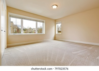 Light empty bedroom interior with soft sand beige walls paint color, walk in closet and wall to wall carpet. Northwest, USA