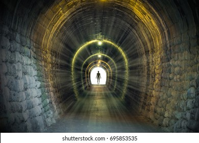 Light at the end of ancient narrow tunnel with man silhouette standing. Life after death, problem solving conceptual illustration