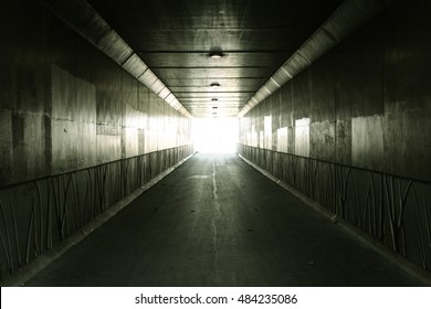 Light At The End Of The Tunnel. Light illuminates the end of a concrete tunnel. In panoramic orientation with copy space.
