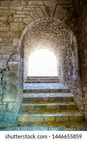 A light in the end of a tunnel in a medieval castle. Illuminated corridor with a arch opening to the light. Abstract and success concept.