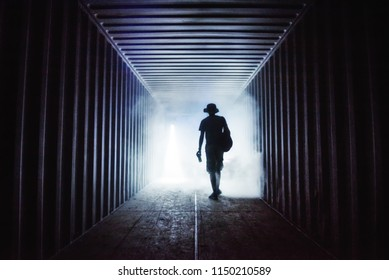 Light at the end of the tunnel. Silhouette of a man in an underground passage