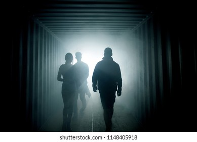 Light at the end of the tunnel. Silhouette of people in misty in underground corridor