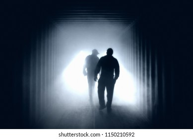 Light at the end of the tunnel. Silhouette of people in an underground passage