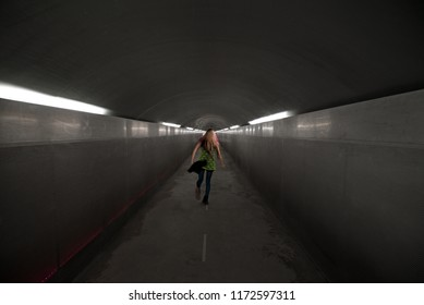 Light at the end of the tunnel. Young Caucasian girl dancing and twirling in a modern concrete underground tunnel that brings to an elevator to the surface. Concept of running away and escape.