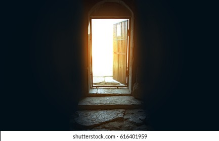 Light entering through open door to a dark empty room