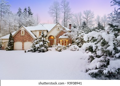 Light fades as night falls on a snowy suburban home
