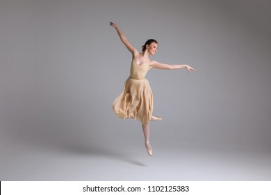 As light as a feather! Young attractive graceful gentle ballerina dancing in the art performance on the isolated background.